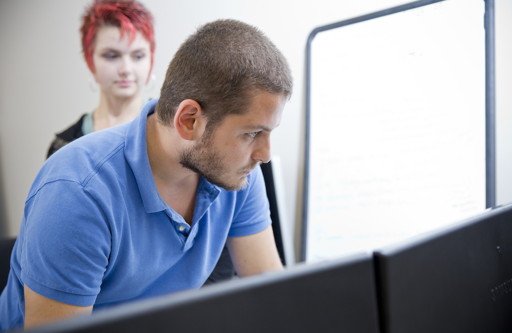 Two students looking intently at a computer.