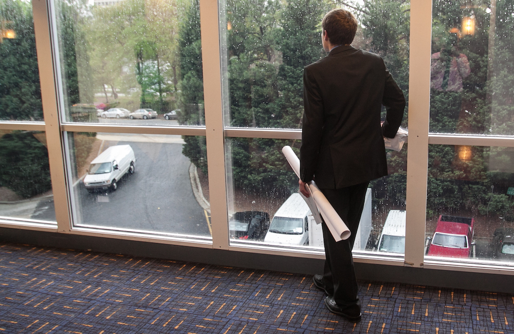 Student holding his research poster at the symposium, looking out a window.