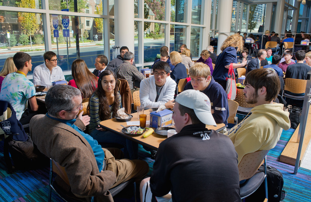 A large group of students and faculty in discussion at the dining hall.