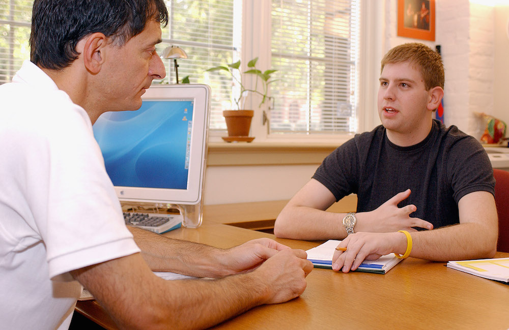 An undergraduate coordinator sitting with a student in his office.